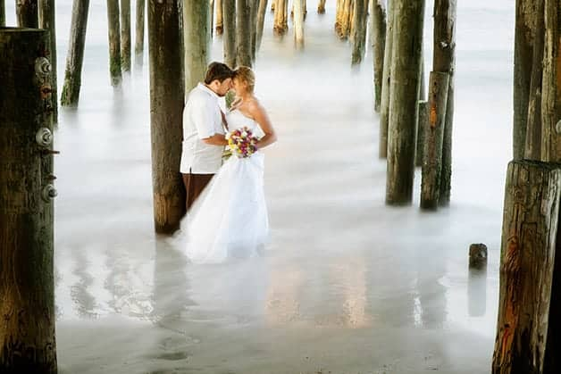 example of long exposure wedding photography to photograph a bride and groom under a wooden pier