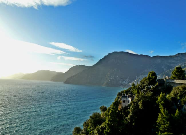 sun starting to set over mountain cliffs amalfi coast by Eileen Cotter Wright