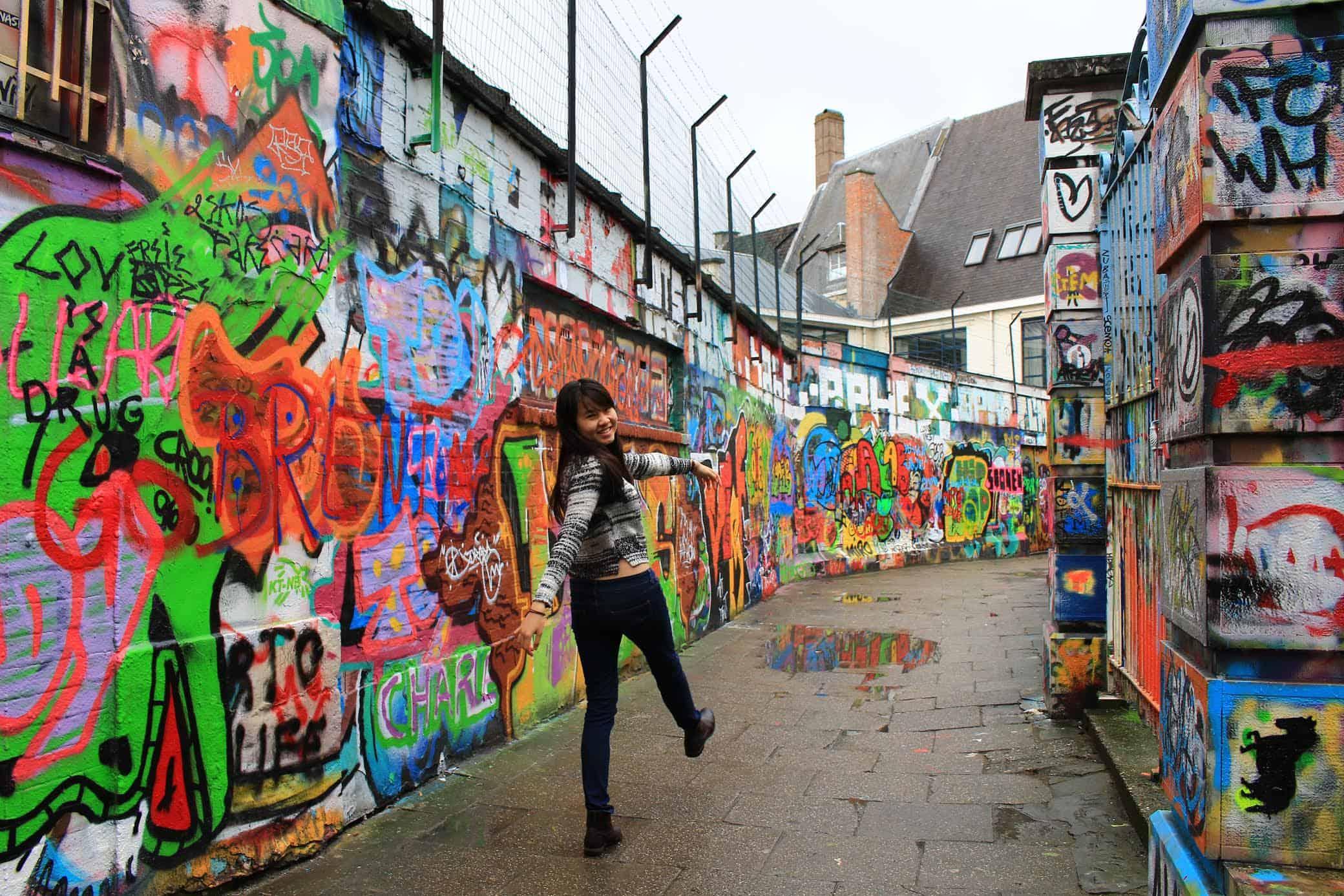 asian girl standing near graffiti in ghent, belguim